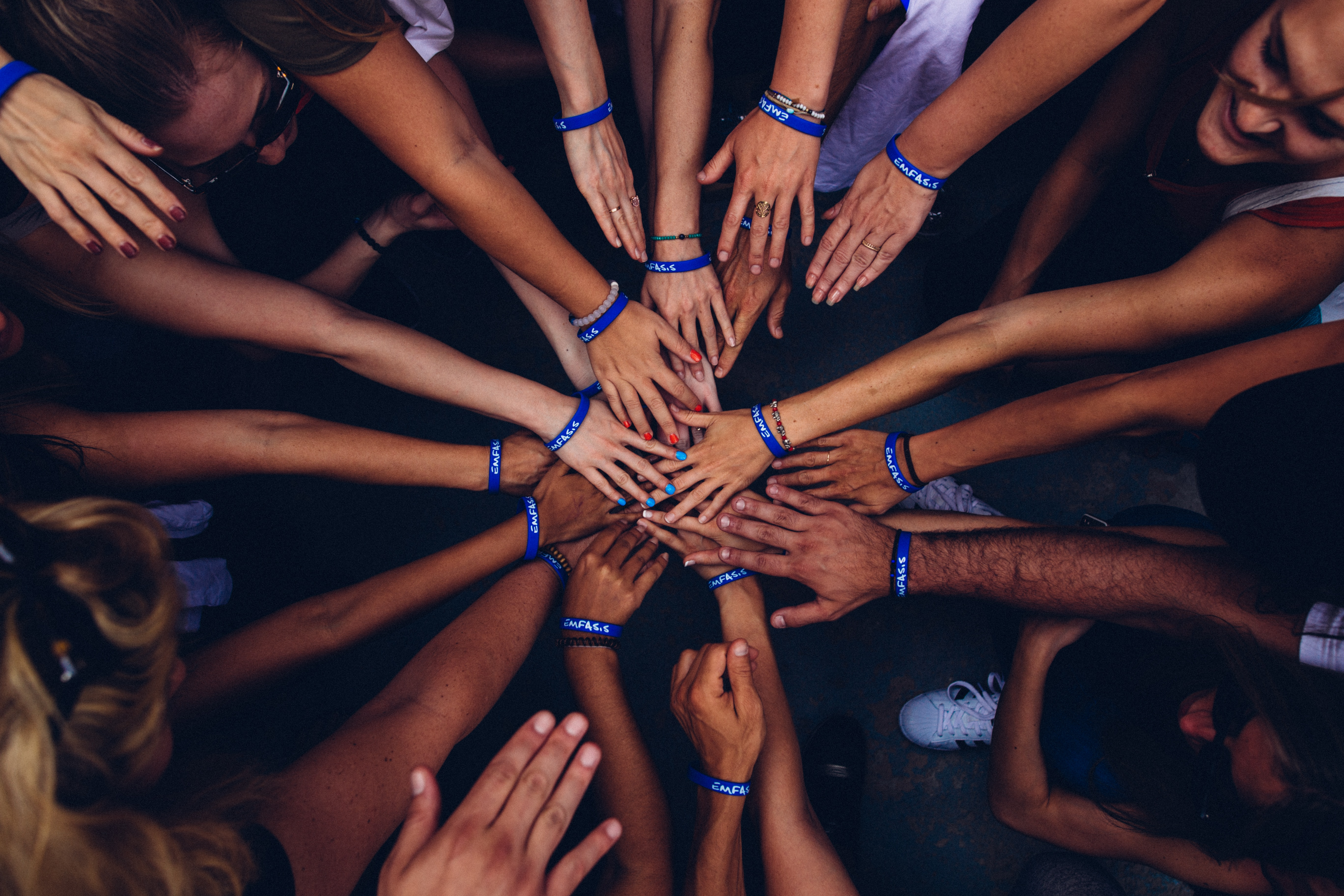 "Many hands together in a ""go team!"" gesture"